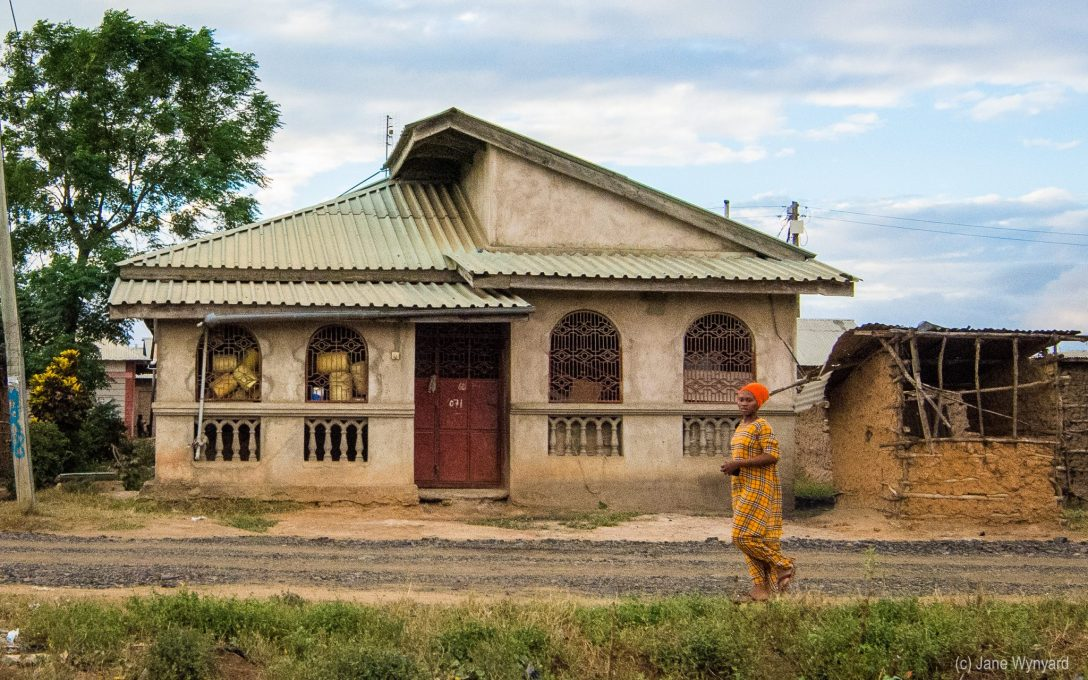 women in yellow outside house kenya